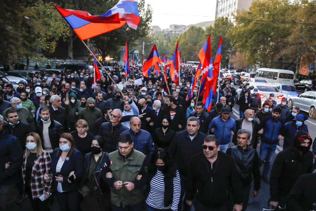 Protesters with Armenian flags walk along a street during a protest against an agreement to halt fighting over the Nagorno-Karabakh region, in Yerevan, Armenia on Nov. 12, 2020. (AP Photo/Dmitri Lovetsky)