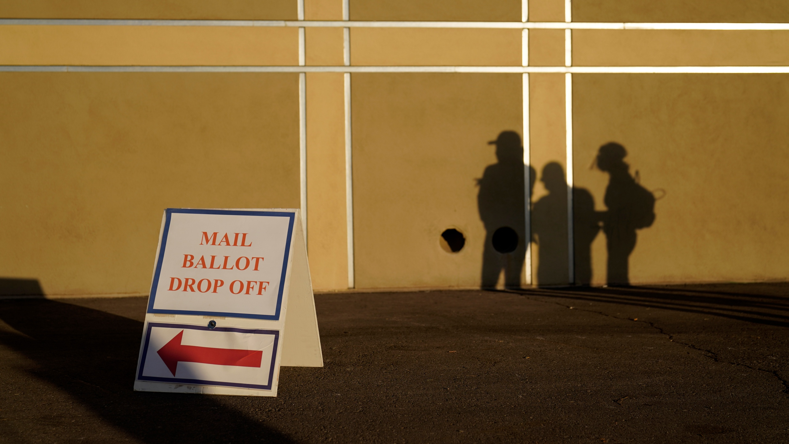 In this Nov. 3, 2020, file photo people wait outside of a polling place on Election Day in Las Vegas. Nevada election law stipulates that in order to register to vote, an individual must have been a resident for 30 days preceding an election, but does not specify how long an already registered voter must be physically present in the state in order to participate in an election. (AP Photo/John Locher, File)