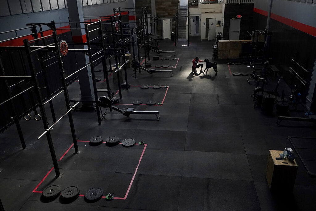 CrossFit Golden Gate owner Danielle Rabkin plays with her dog Bruno while interviewed at her gym in San Francisco on Nov. 12, 2020. (AP Photo/Jeff Chiu)