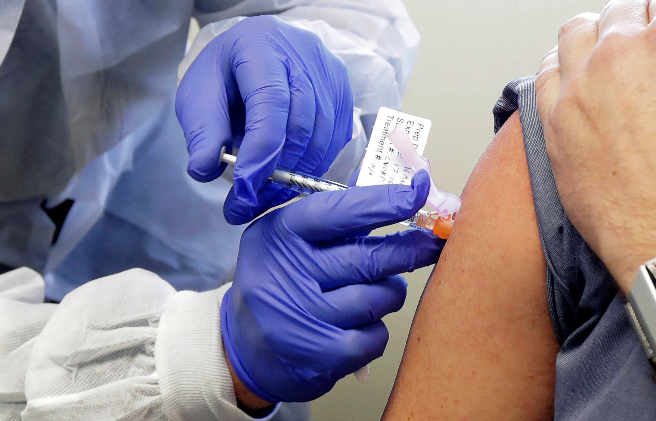 In this Monday, March 16, 2020 file photo, Neal Browning receives a shot in the first-stage safety study clinical trial of a potential vaccine for COVID-19, the disease caused by the new coronavirus at the Kaiser Permanente Washington Health Research Institute in Seattle. (Ted S. Warren/AP Photo)