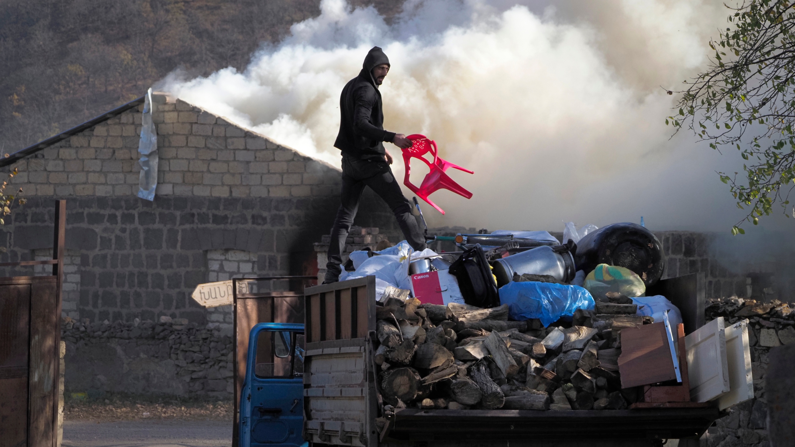 A man loads possessions on his truck after setting his home on fire, in an area once occupied by Armenian forces but is soon to be turned over to Azerbaijan, in Karvachar, the separatist region of Nagorno-Karabakh, on Friday, Nov. 13, 2020. (Dmitry Lovetsky/AP Photo)