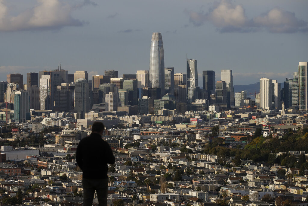 In this March 16, 2020, file photo, a man looks toward the skyline from Bernal Heights Hill in San Francisco. (AP Photo/Jeff Chiu, File)