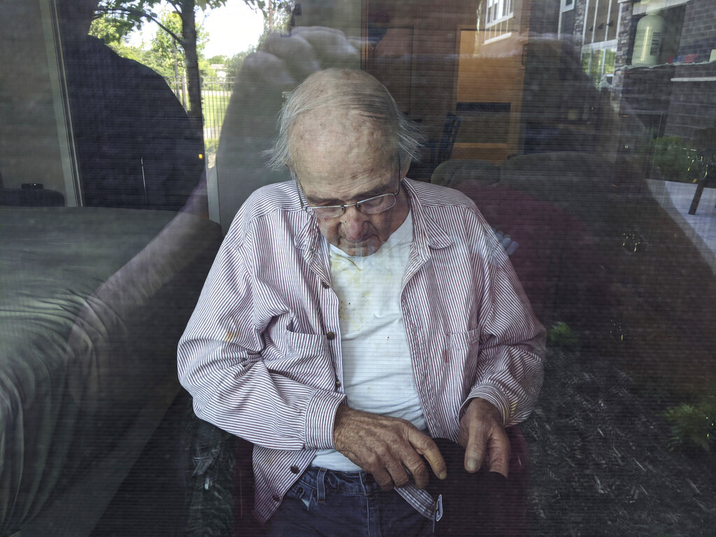 This June 7, 2020, photo provided by June Linnertz shows her father, James Gill, seen through a window at Cherrywood Pointe nursing home in Plymouth, Minn. (June Linnertz via AP)
