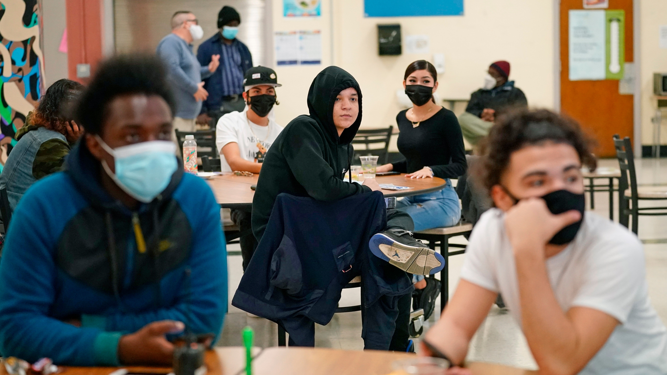 In this Oct. 29, 2020, file photo, students at West Brooklyn Community High School listen to questions posed by their principal during a current events-trivia quiz and pizza party in the school's cafeteria in New York. (AP Photo/Kathy Willen, File)