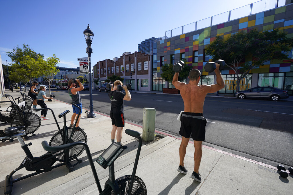In this Aug. 12, 2020, file photo, people lift weights outdoors while training at Invictus Fitness in San Diego. The gym was forced to push their workouts outdoors after the city's closure of many indoor activities to slow the spread of the coronavirus. Four San Diego County restaurants and gyms that were forced to halt indoor operations beginning Nov. 14, have filed a lawsuit seeking an emergency injunction to halt the shutdown. (AP Photo/Gregory Bull, File)