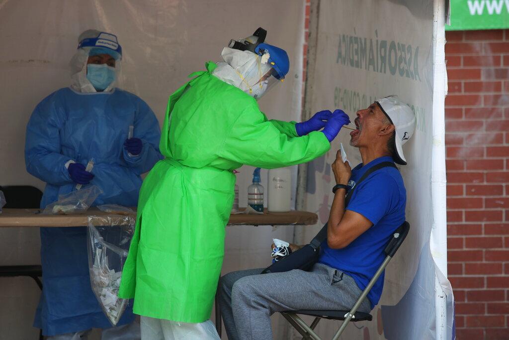 A healthcare worker tests a person for the new coronavirus inside a diagnostic tent in Mexico City, Saturday, Nov. 14, 2020. (AP Photo/Ginnette Riquelme)