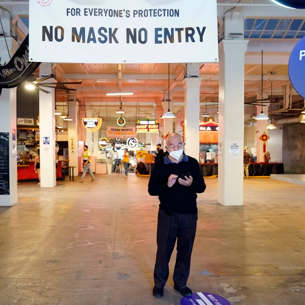 sign points to a mask mandate at the Grand Central Market, Monday, Nov. 16, 2020, in Los Angeles. Gov. Gavin Newsom announced Monday, Nov. 16, 2020, that due to the rise of COVID-19 cases, some counties have been moved to the state's most restrictive set of rules, which prohibit indoor dining. The new rules begin Tuesday, Nov. 17. (AP Photo/Marcio Jose Sanchez)