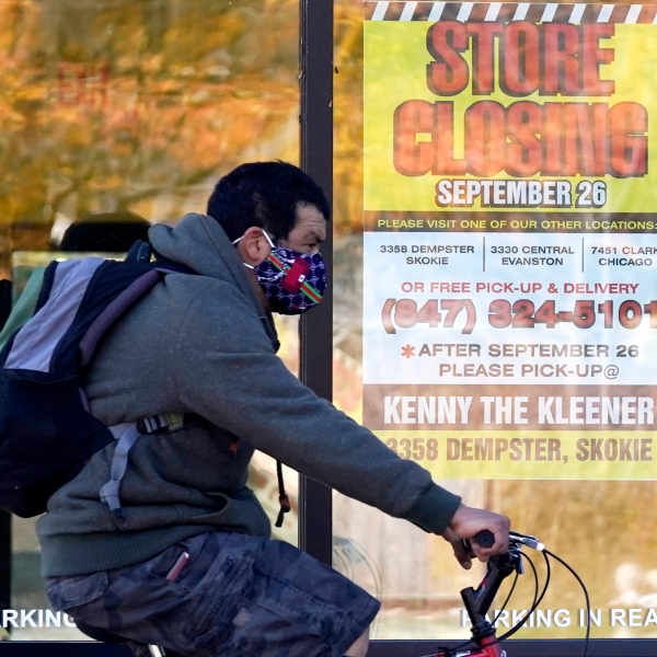 In this Friday, Nov. 6, 2020, file photo, a man wearing a face mask rides a bicycle past a closed store in Wilmette, Ill. (AP Photo/Nam Y. Huh, File)