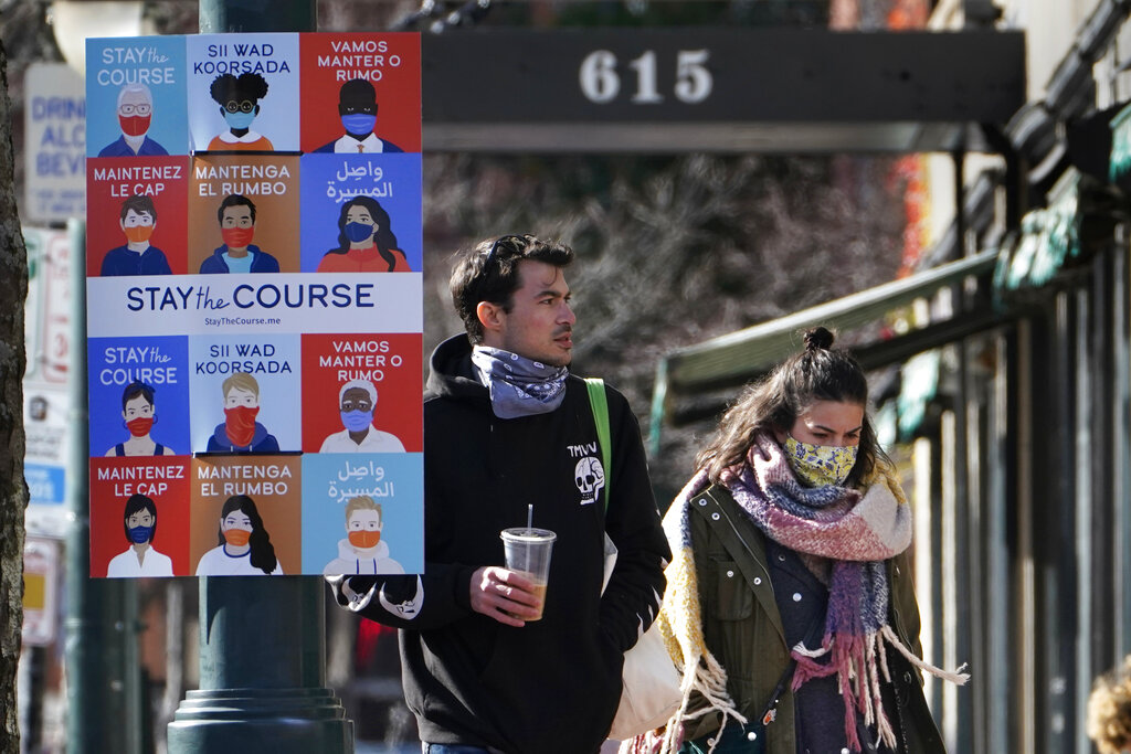 A sign in multiple languages encourages citizens to wear face coverings to help prevent the spread of COVID-19, Tuesday, Nov. 17, 2020, in Portland, Maine. (AP Photo/Robert F. Bukaty)