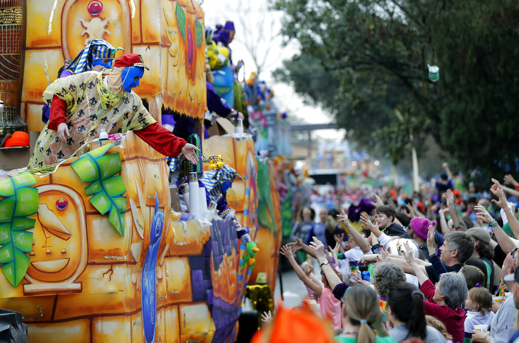 In this Feb. 11, 2018, file photo, float riders toss beads and trinkets during the Krewe of Thoth Mardi Gras parade in New Orleans. (AP Photo/Gerald Herbert, File)