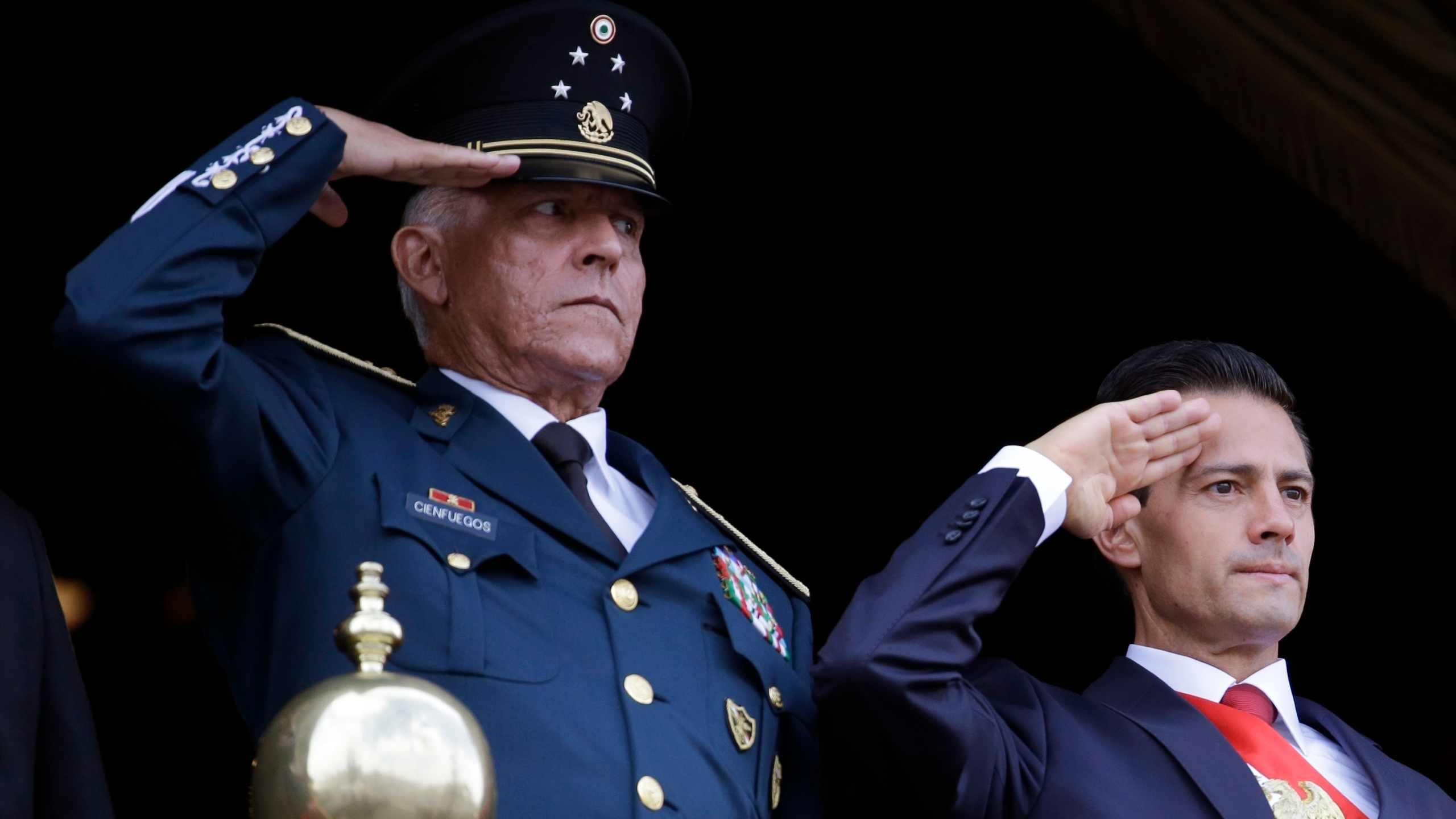 In this Sept. 16, 2016, file photo, Defense Secretary Gen. Salvador Cienfuegos, left, and Mexico's President Enrique Pena Nieto, salute during the annual Independence Day military parade in Mexico City's main square. (Rebecca Blackwell / Associated Press)