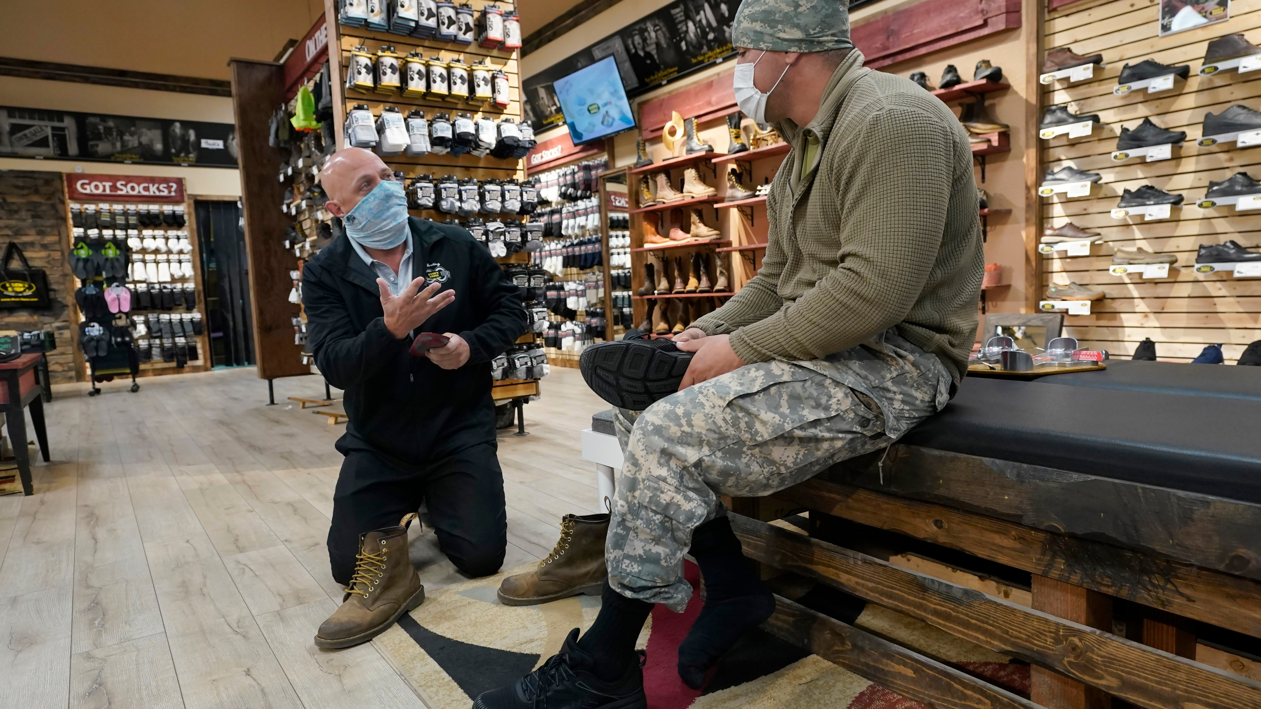 Patrick Marks, left, helps customer Jesus Chavez at Beck's Shoes in the Sutter County committee of Yuba City, Calif., on Nov. 17, 2020. (Rich Pedroncelli / Associated Press)