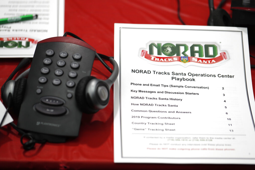 In this Dec. 23, 2019, file photo a playbook sits next to a telephone set up in the NORAD Tracks Santa center at Peterson Air Force Base in Colorado Springs, Colo. (AP Photo/David Zalubowski, File)