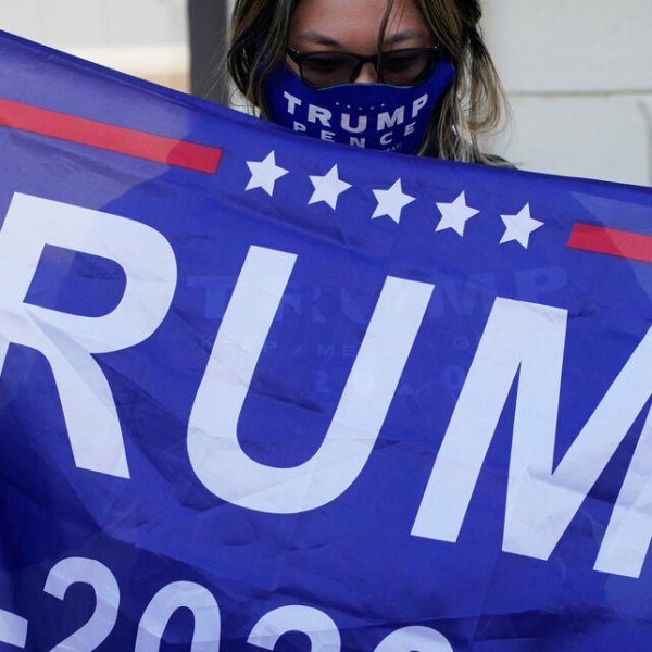 A supporter of President Donald Trump holds a flag during a news conference Tuesday, Nov. 17, 2020, in Las Vegas. (AP Photo/John Locher)