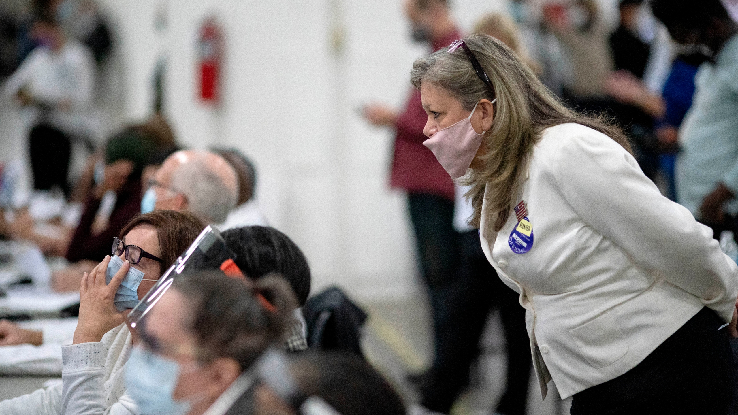 In this Nov. 4, 2020, file photo, a Republican election challenger at right watches over election inspectors as they examine a ballot as votes are counted into the early morning hours at the central counting board in Detroit. (AP Photo/David Goldman, File)
