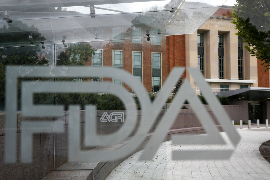This Thursday, Aug. 2, 2018, file photo shows the U.S. Food and Drug Administration building behind FDA logos at a bus stop on the agency's campus in Silver Spring, Md.(AP Photo/Jacquelyn Martin, File)