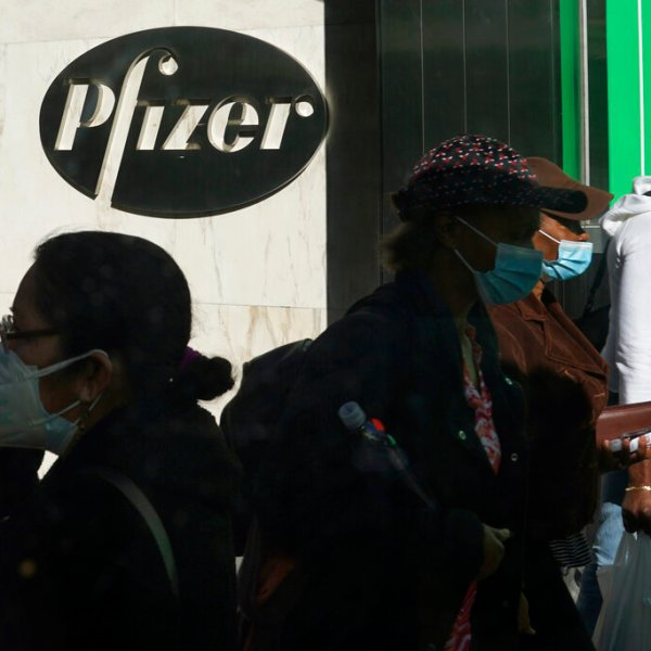 In this Nov. 9, 2020, file photo, pedestrians walk past Pfizer world headquarters in New York. (AP Photo/Bebeto Matthews, File)