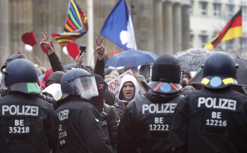 A protestor shouts as people attend a protest rally in front of the Brandenburg Gate in Berlin, Germany, Wednesday, Nov. 18, 2020 against the coronavirus restrictions in Germany. (AP Photo/Michael Sohn)