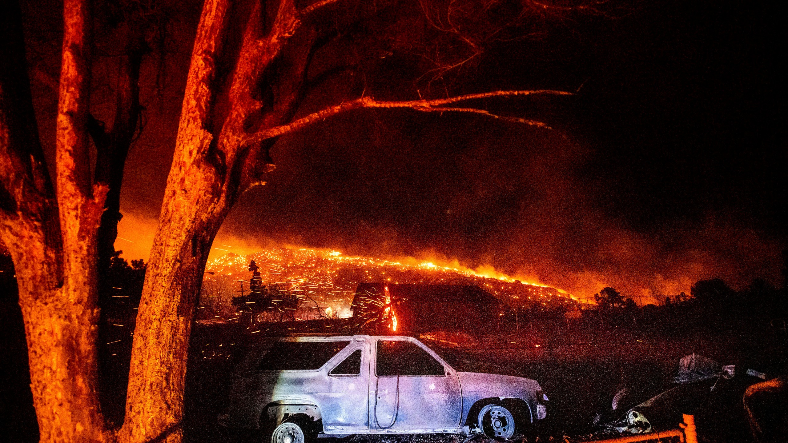 A scorched vehicle rests in a yard as the Mountain View Fire tears through the Walker community in Mono County, on Tuesday, Nov. 17, 2020. (AP Photo/Noah Berger)