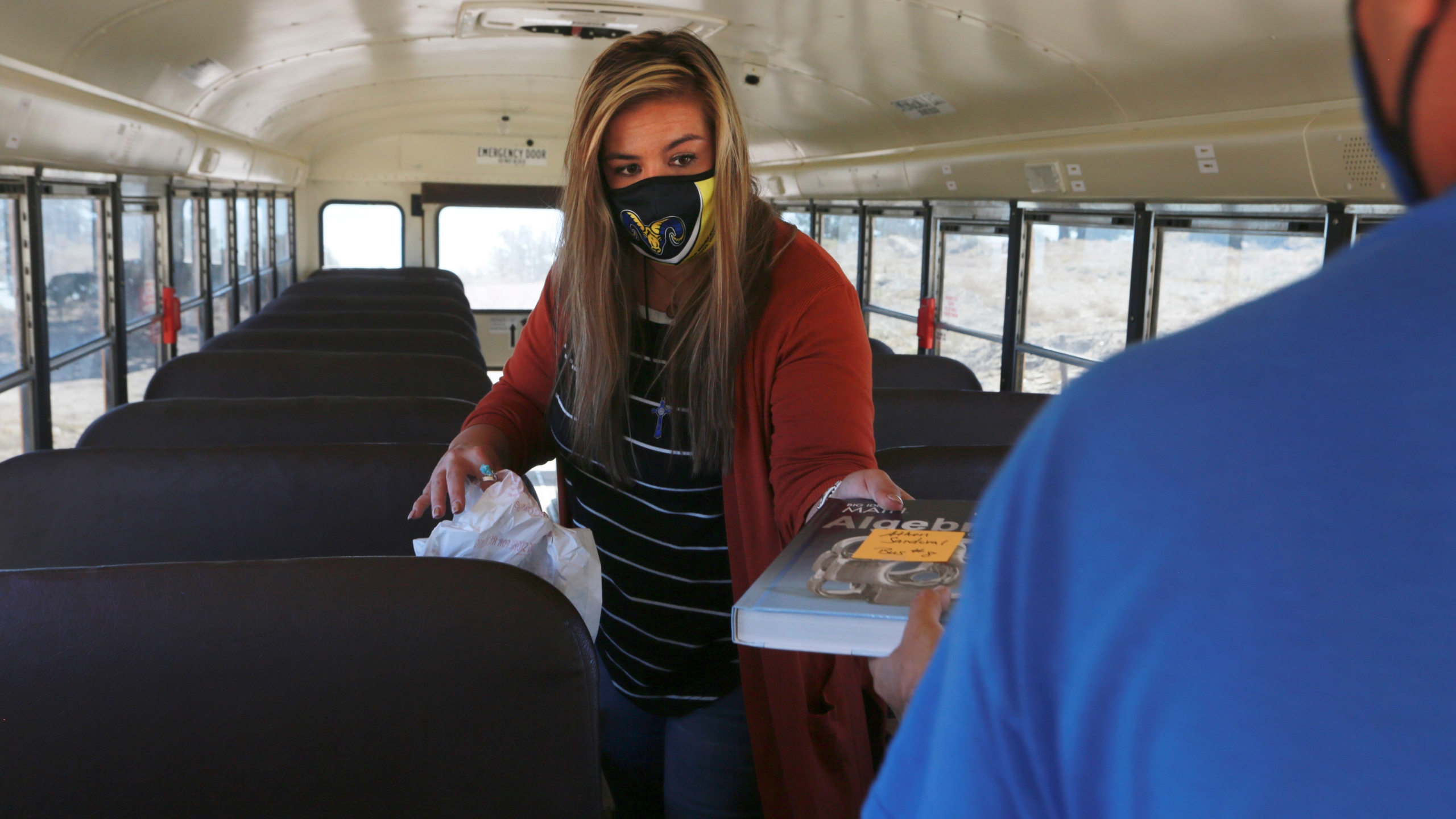 Social worker Victoria Dominguez hands school bus driver Kelly Maestas a school math book for a student at a stop outside Cuba, N.M., Oct. 19, 2020. (Cedar Attanasio/AP Photo)