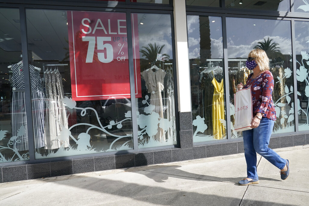 A shopper walks by a store, Monday, Nov. 18, 2020 in Pembroke Pines, Fla. (AP Photo/Marta Lavandier)