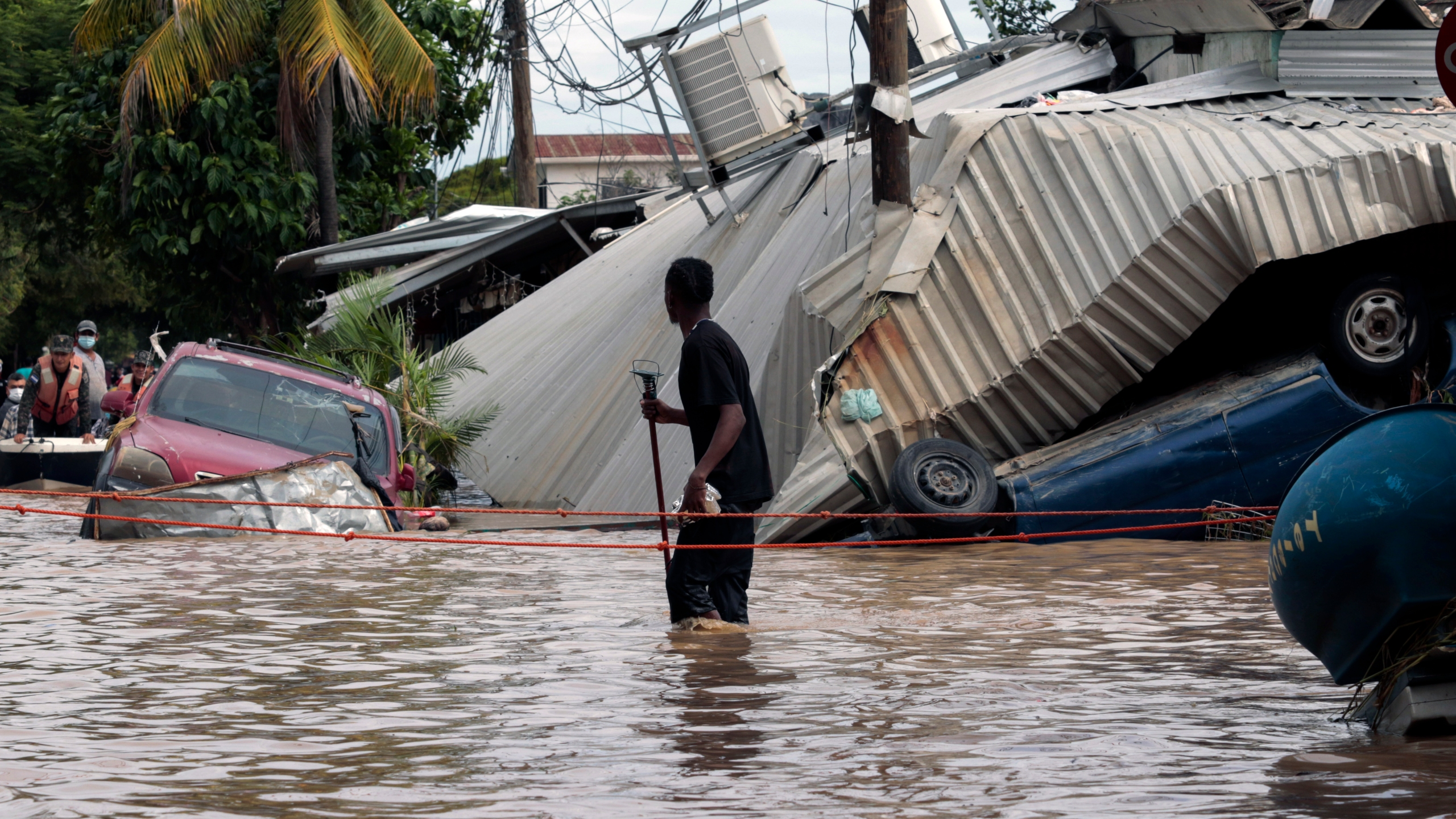 In this Nov. 6, 2020 file photo, a resident walking through a flooded street looks back at storm damage caused by Hurricane Eta in Planeta, Honduras. Flooded out Honduran and Guatemalan families stranded on rooftops in the most marginalized neighborhoods after the passage of hurricanes Eta and Iota portend a new wave of migration, observers across the region say. (AP Photo/Delmer Martinez, File)