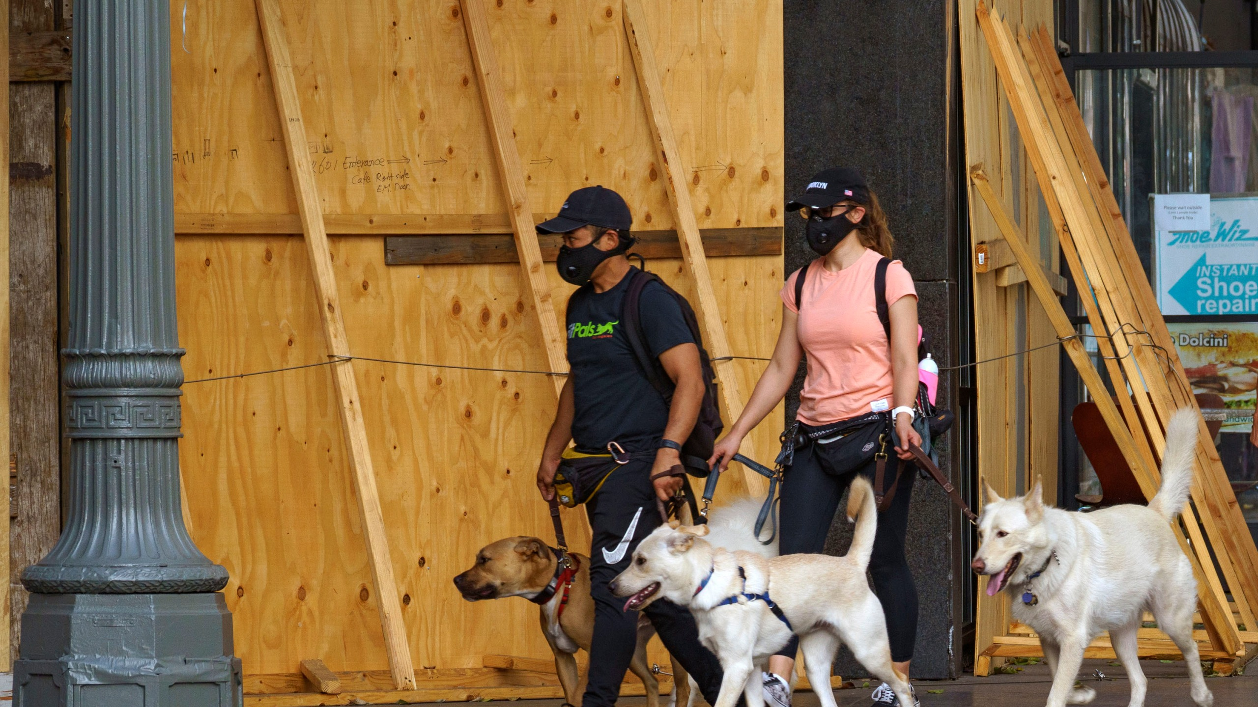 Dog walkers wear face masks as they walk around boarded business downtown Los Angeles Wednesday, Nov. 18, 2020. (AP Photo/Damian Dovarganes)
