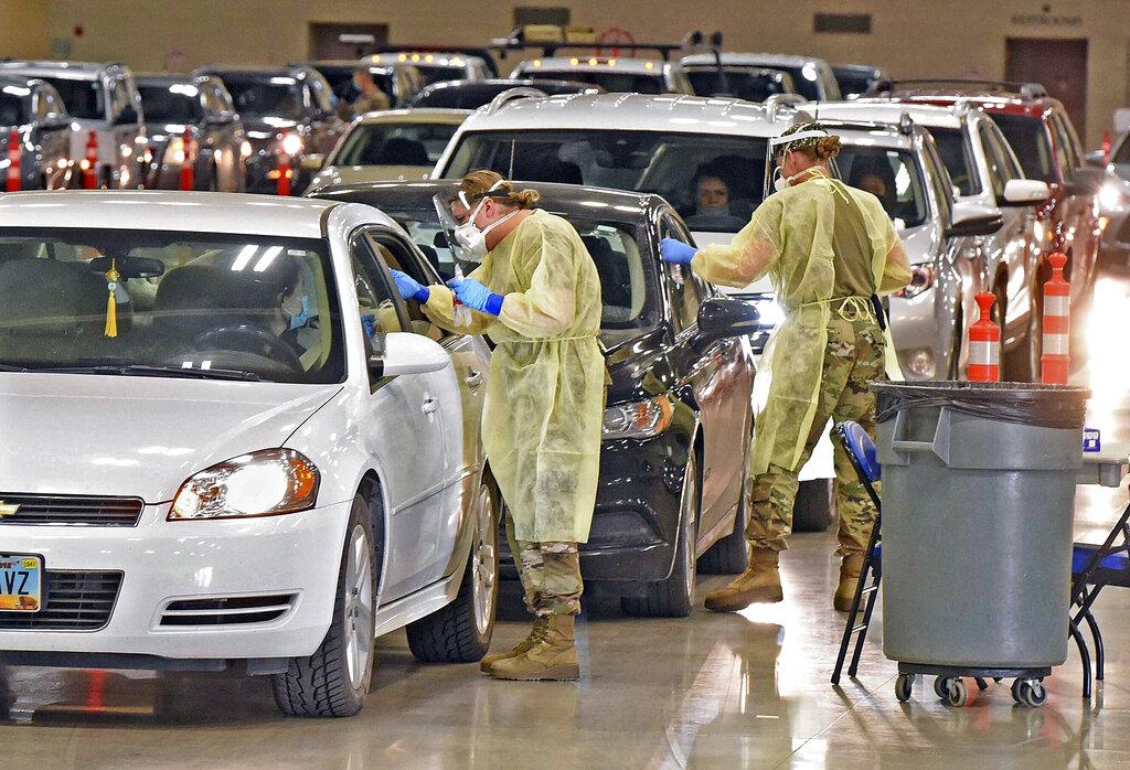 In this Nov. 17, 2020, file photo, North Dakota National Guard soldiers administer coronavirus tests inside the Bismarck Events Center in Bismarck, N.D. (Tom Stromme/The Bismarck Tribune via AP, File)