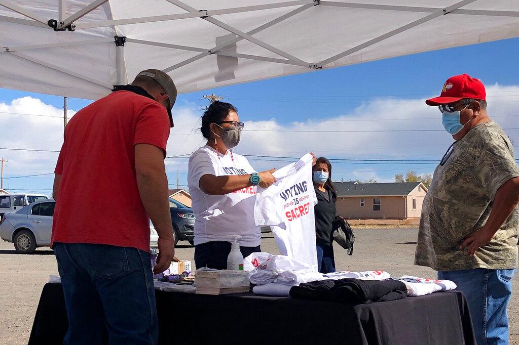 This photo provided by Carol Davis shows Cherilyn Yazzie speaking to a voter on Nov. 3, 2020, in the Navajo community of Dilkon in northeastern Arizona. (Carol Davis via AP)