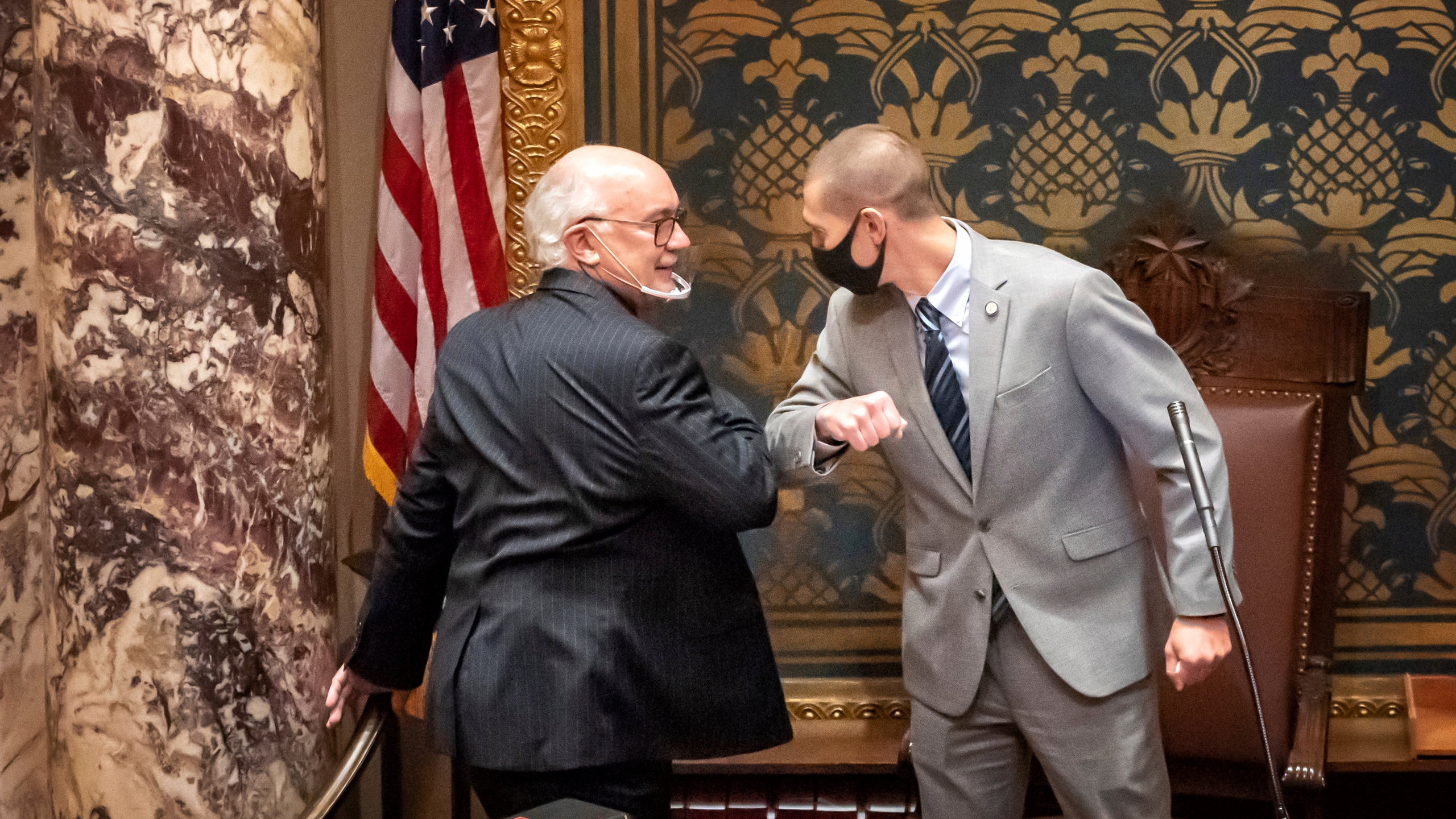 In this Nov. 12, 2020 file photo, outgoing Minnesota State Senate President Senate President Jeremy Miller, R-Winona gave Sen. David Tomassoni, DFL-Chisholm a congratulatory elbow bump before Tomassoni addressed the Senate Chamber in St. Paul, Minn. At least 187 state legislators nationwide have tested positive for the virus and four have died since the pandemic began, according to figures compiled by The Associated Press. Twelve Arkansas lawmakers have tested positive for the virus over the past month, the second largest known outbreak in a state legislature. (Glen Stubbe/Star Tribune via AP)