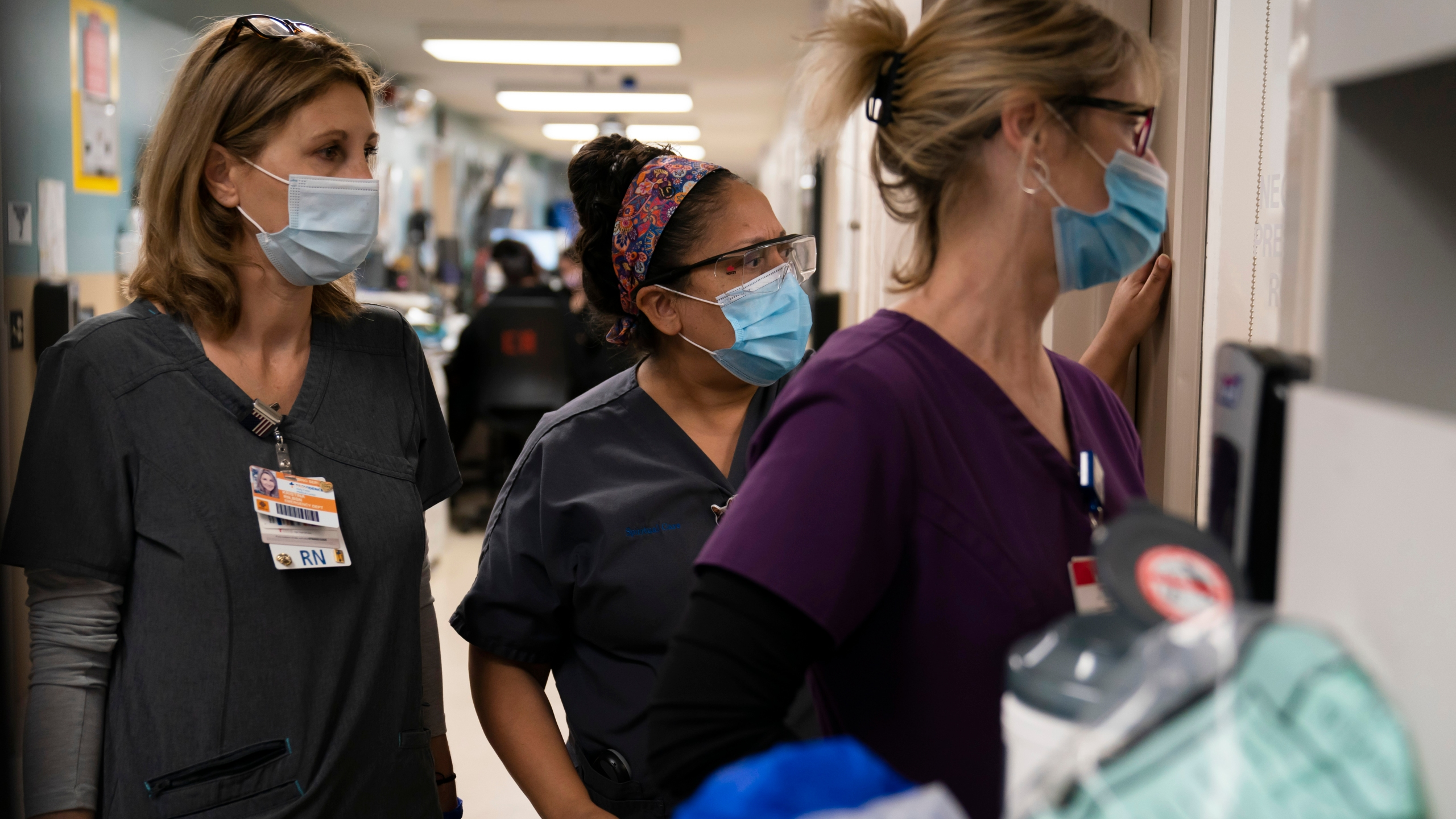 """Registered Nurse Kristina Shannon, from left, chaplain Andrea Cammarota, and Emergency Room charge nurse Cathy Carter watch as medical workers try to resuscitate a patient who tested positive for coronavirus in the emergency room at Providence Holy Cross Medical Center in the Mission Hills section of Los Angeles, Thursday, Nov. 19, 2020. """"I think ER nurses are a special breed,"""" said Shannon. """"At that moment, you are just doing your job. You try not to think of the fact that that's somebody's mother, grandmother, or wife laying in there."""" (AP Photo/Jae C. Hong)"""