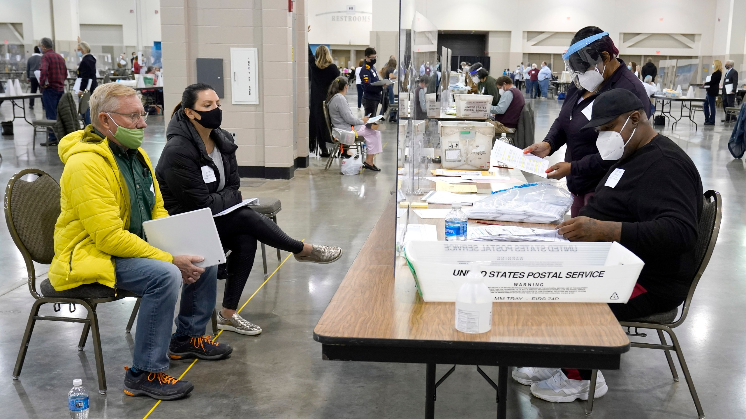 Election workers, right, verify ballots as recount observers, left, watch during a Milwaukee hand recount of presidential votes at the Wisconsin Center, Friday, Nov. 20, 2020, in Milwaukee. (AP Photo/Nam Y. Huh)