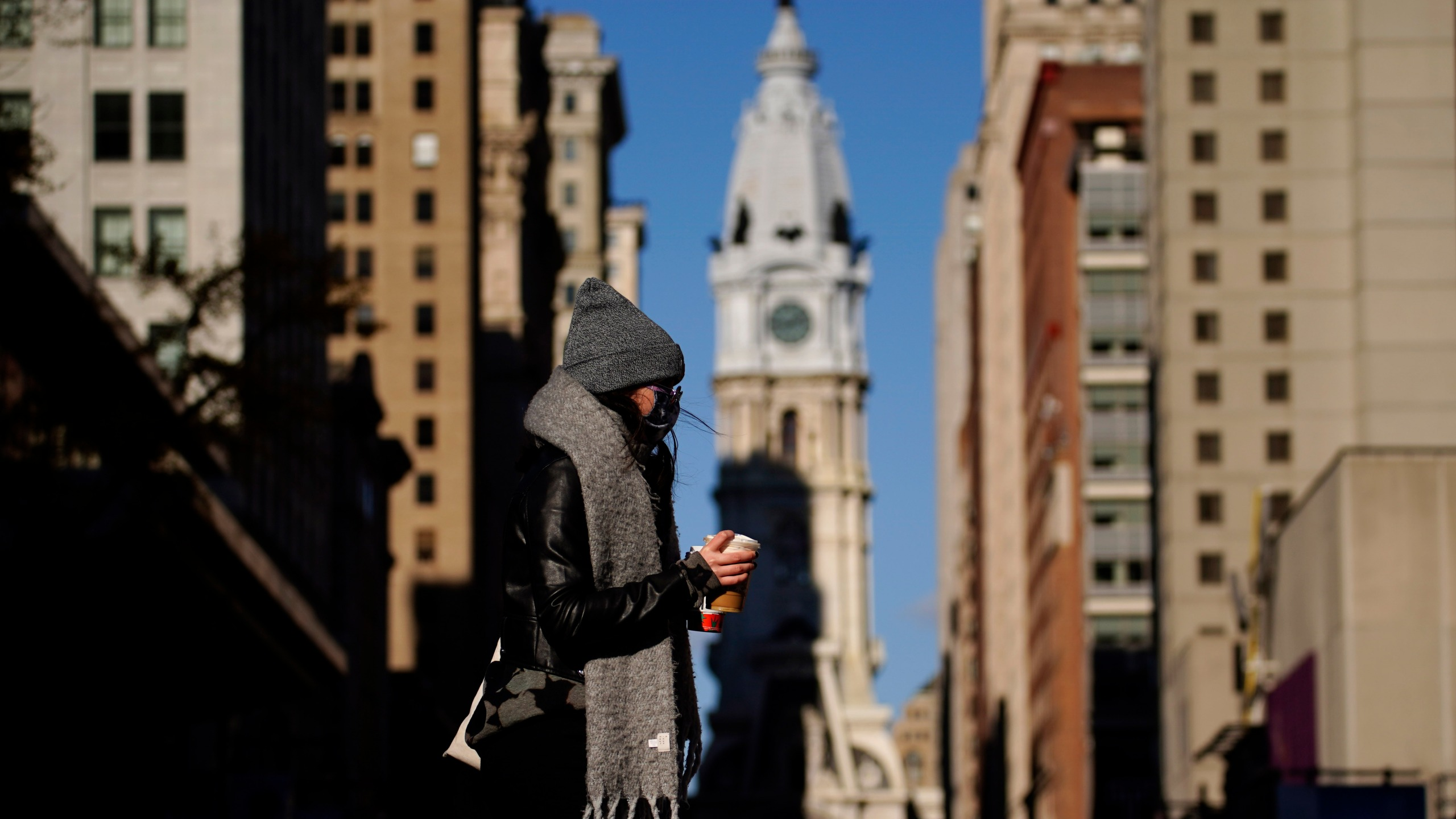In this Nov. 18, 2020, photo, a person wearing a face mask crosses Broad Street in Philadelphia. (AP Photo/Matt Slocum)