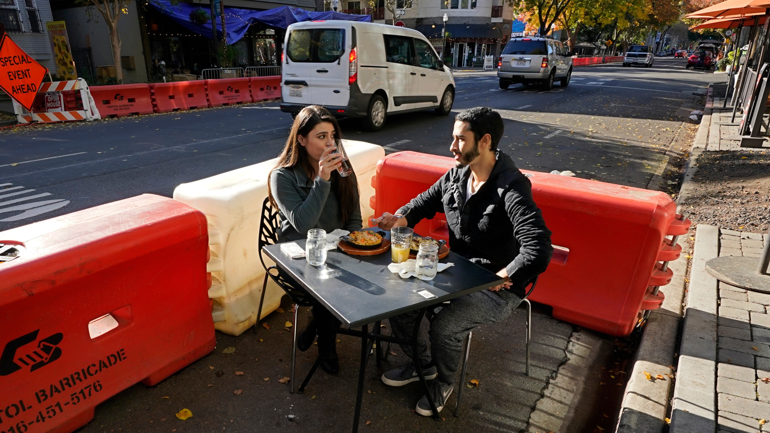 Ranim Abaad and Joey Bettencourt, right, have lunch at the RIND in Sacramento on Nov. 20, 2020. (Rich Pedroncelli / Associated Press)