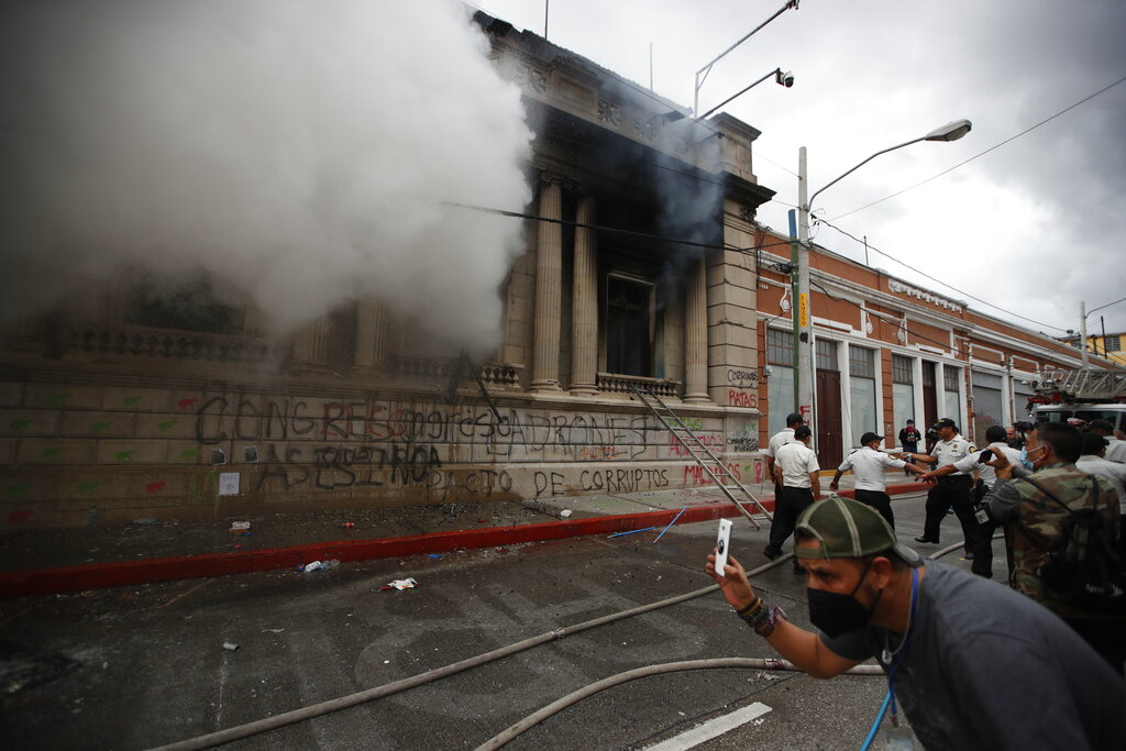 Clouds of smoke shoot out from the Congress building after protesters set it on fire, in Guatemala City, on Nov. 21, 2020. (AP Photo/Moises Castillo)