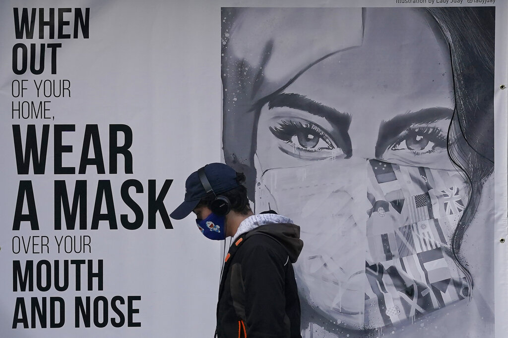 A pedestrian walks past a sign advising mask-wearing during the coronavirus outbreak in San Francisco on Nov. 21, 2020. (AP Photo/Jeff Chiu)