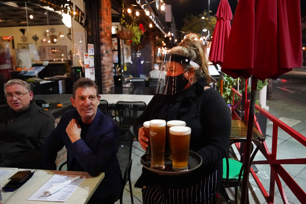 In this Nov. 19, 2020, file photo, a waitress serves beer to patrons at Ye Olde King's Head in Santa Monica, Calif. (AP Photo/Marcio Jose Sanchez, File)