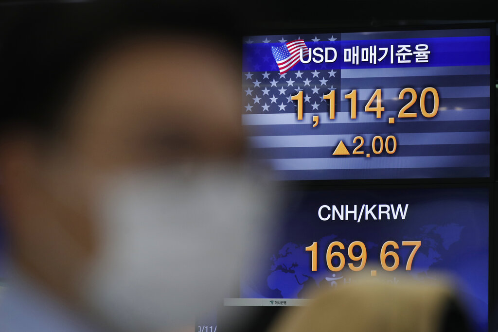 A currency trader watches computer monitors near screens showing the foreign exchange rates at the foreign exchange dealing room in Seoul, South Korea, Monday, Nov. 23, 2020. (AP Photo/Lee Jin-man)