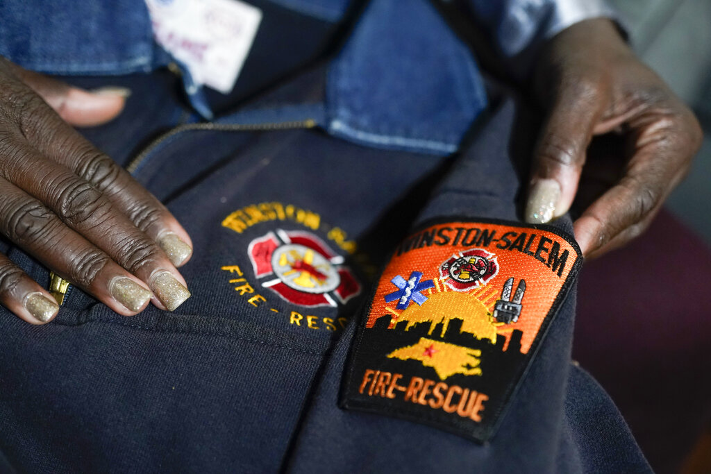 Timika Ingram holds a jacket she had when she was a firefighter on Nov. 19, 2020, in Charlotte, N.C. (AP Photo/Chris Carlson)