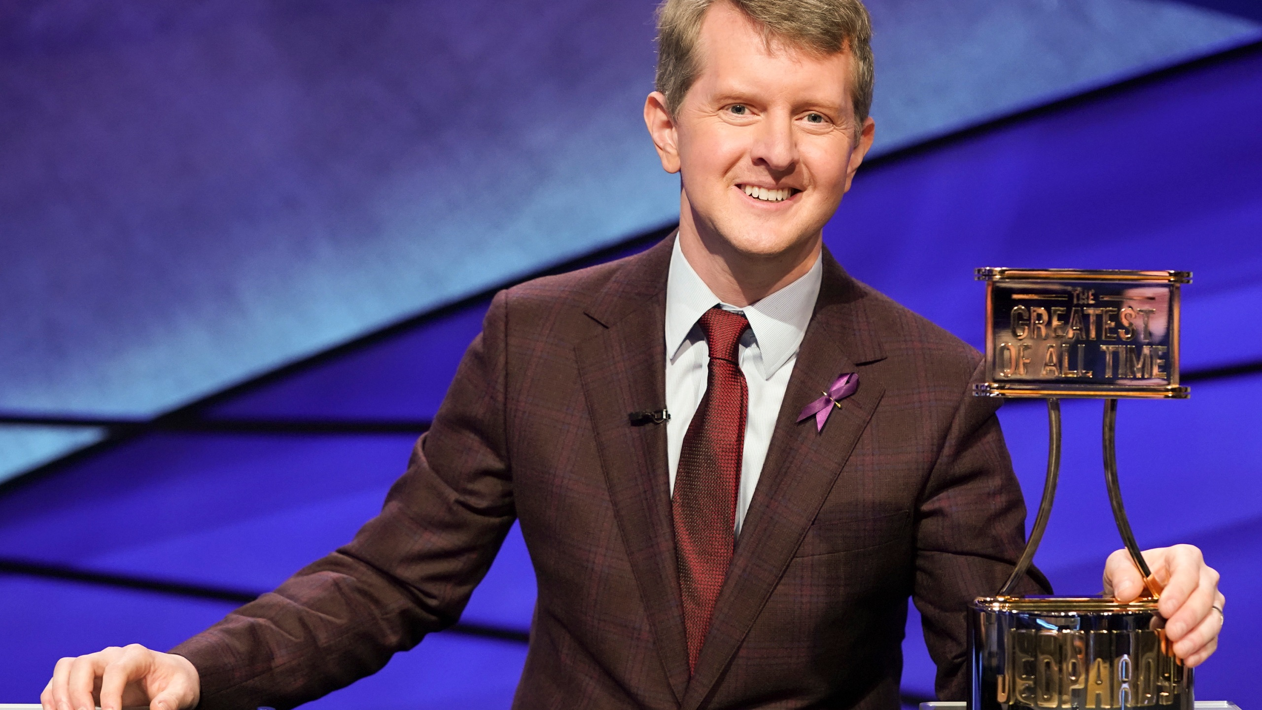"This image released by ABS shows contestant Ken Jennings with a trophy on ""JEOPARDY! The Greatest of All Time."" (Eric McCandless / ABC via Associated Press)"