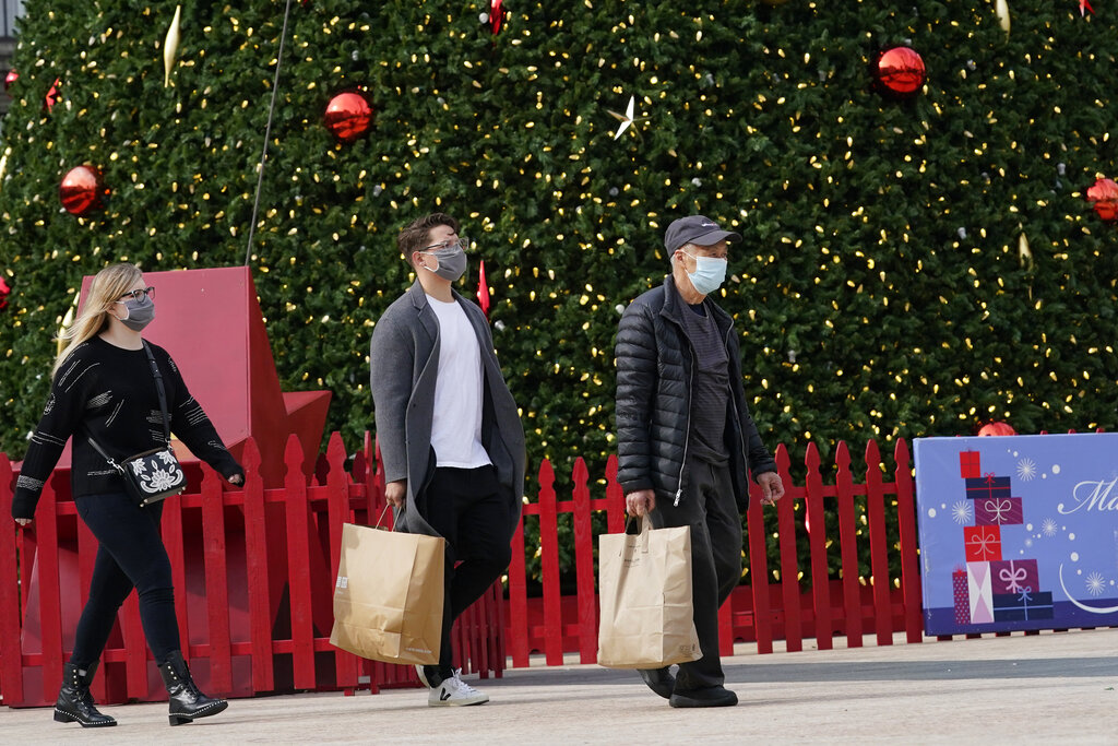 People carry shopping bags while walking past the annual Macy's Great Tree at Union Square during the coronavirus outbreak in San Francisco on Nov. 21, 2020. (AP Photo/Jeff Chiu)