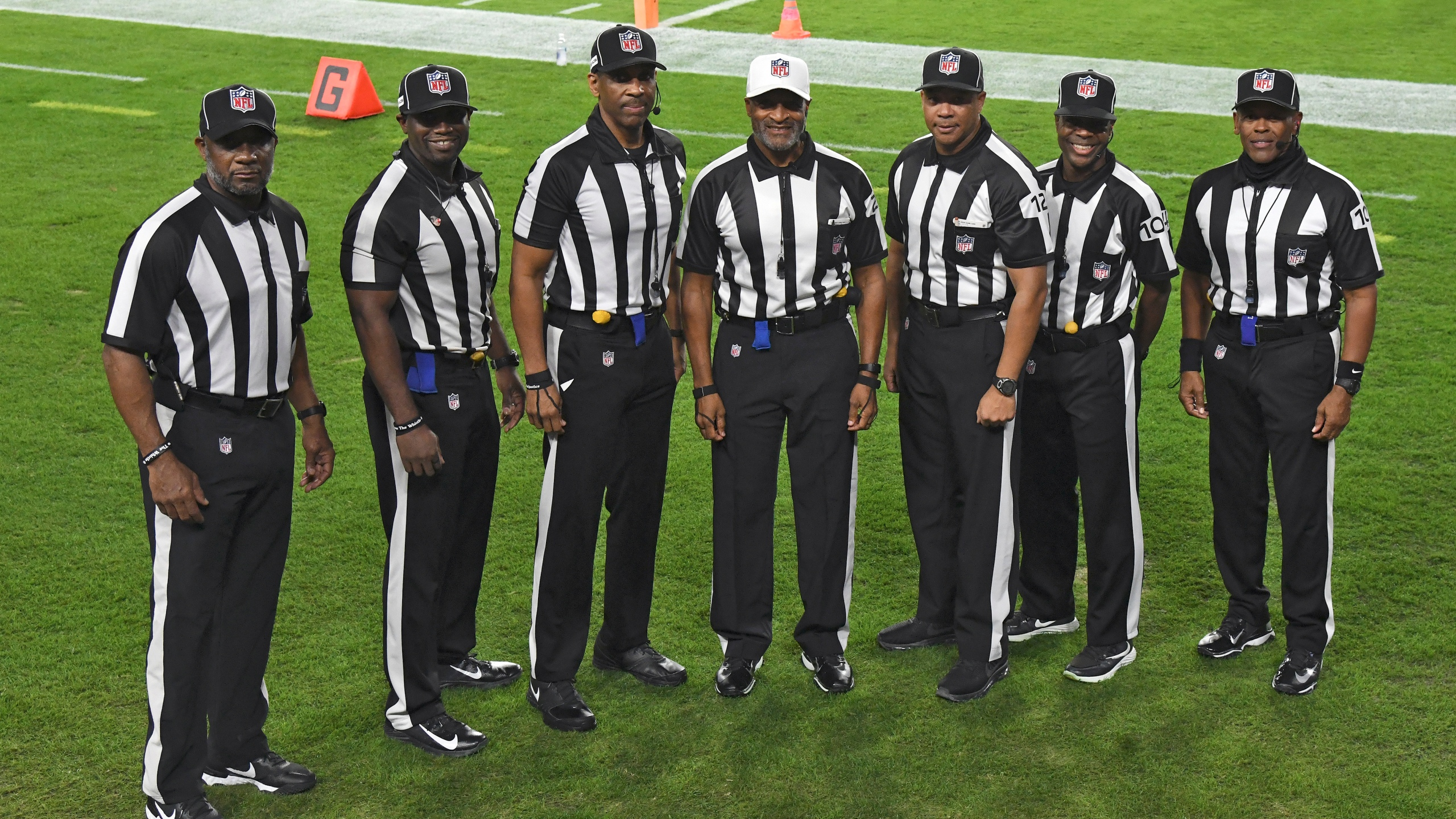 NFL officials, from left, umpire Barry Anderson, side judge Anthony Jeffries, down judge Julian Mapp, referee Jerome Boger, back judge Greg Steed, field judge Dale Shaw (104), line judge Carl Johnson (101) pose for a photo before an NFL football game between the Tampa Bay Buccaneers and the Los Angeles Rams on Nov. 23, 2020, in Tampa, Fla. The game is the first in NFL history to feature an all African-American officiating crew. (AP Photo/Jason Behnken)