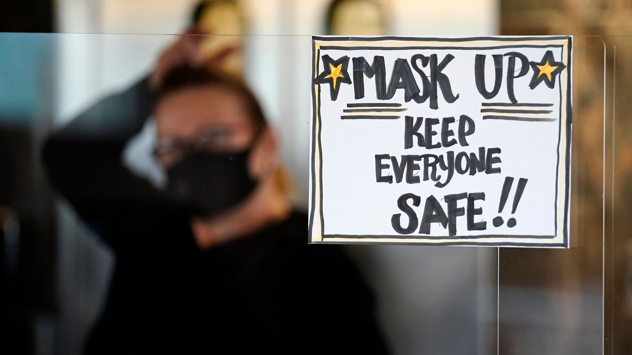 In this Tuesday, Nov. 17, 2020 file photo, manager Yllka Murati waits for a delivery driver to pick up takeout orders behind a partition displaying a sign to remind customers to wear a mask, at the Penrose Diner, in south Philadelphia. (AP Photo/Matt Slocum, File)