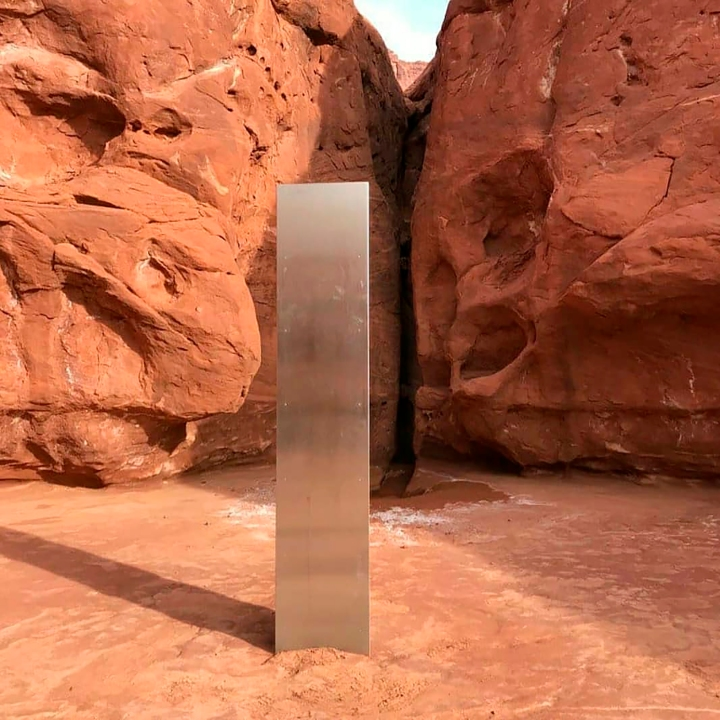 This Nov. 18, 2020 photo provided by the Utah Department of Public Safety shows a metal monolith installed in the ground in a remote area of red rock in Utah. The smooth, tall structure was found during a helicopter survey of bighorn sheep in southeastern Utah, officials said Monday. State workers from the Utah Department of Public Safety and Division of Wildlife Resources spotted the gleaming object from the air and landed nearby to check it out. The exact location is so remote that officials are not revealing it publicly, worried that people might get lost or stranded trying to find it and need to be rescued. (Utah Department of Public Safety via AP)