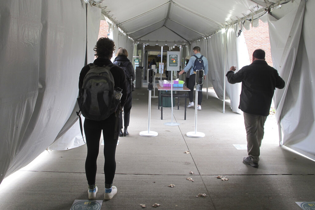 In this Nov. 12, 2020, photo, University of Vermont students walk through a tent leading to a COVID-testing site on campus in Burlington, Vt. As coronavirus cases are surging around the U.S., some colleges and universities are rethinking some of their plans for next semester. (AP Photo/Lisa Rathke)