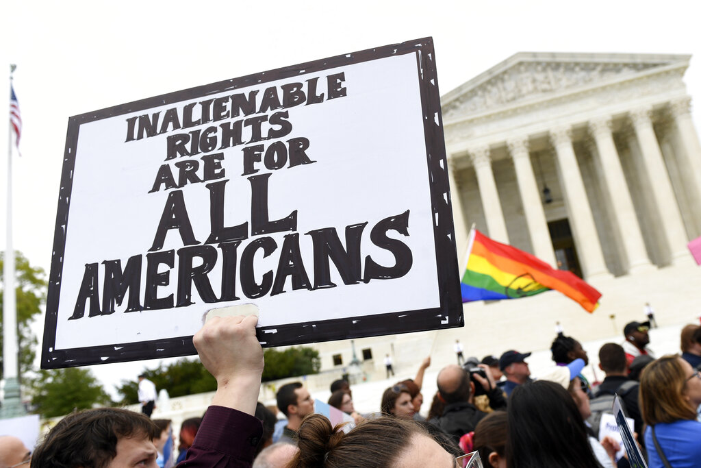 In this Oct. 8, 2019, file photo, protesters gather outside the Supreme Court in Washington where the Supreme Court is hearing arguments in the first case of LGBT rights since the retirement of Supreme Court Justice Anthony Kennedy. (AP Photo/Susan Walsh, File)