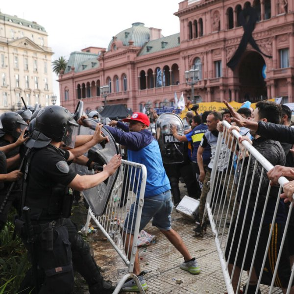 Soccer fans waiting to see Diego Maradona lying in state clash with police outside the presidential palace in Buenos Aires, Argentina, Thursday, Nov. 26, 2020. (AP Photo/Rodrigo Abd)