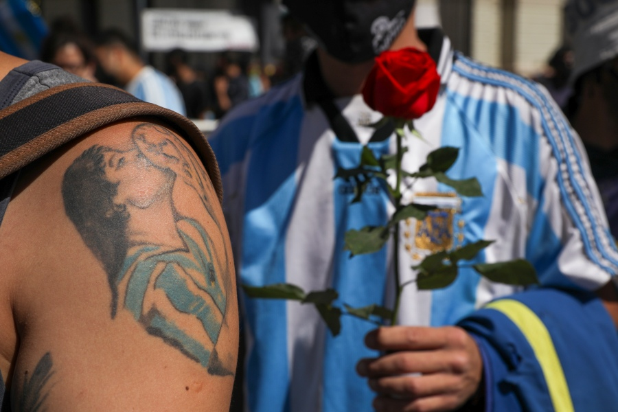 A mourner, sporting a tattoo of Diego Maradona on his forearm, waits in line to pay his final respects to the Argentine soccer great in Buenos Aires, Argentina, on Nov. 26, 2020. (Rodrigo Abd / Associated Press)