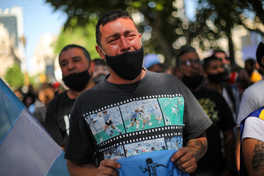 A man cries as he waits in a line outside the presidential palace in Buenos Aires to pay his final respects to Diego Maradona on Nov. 26, 2020. (Rodrigo Abd / Associated Press)
