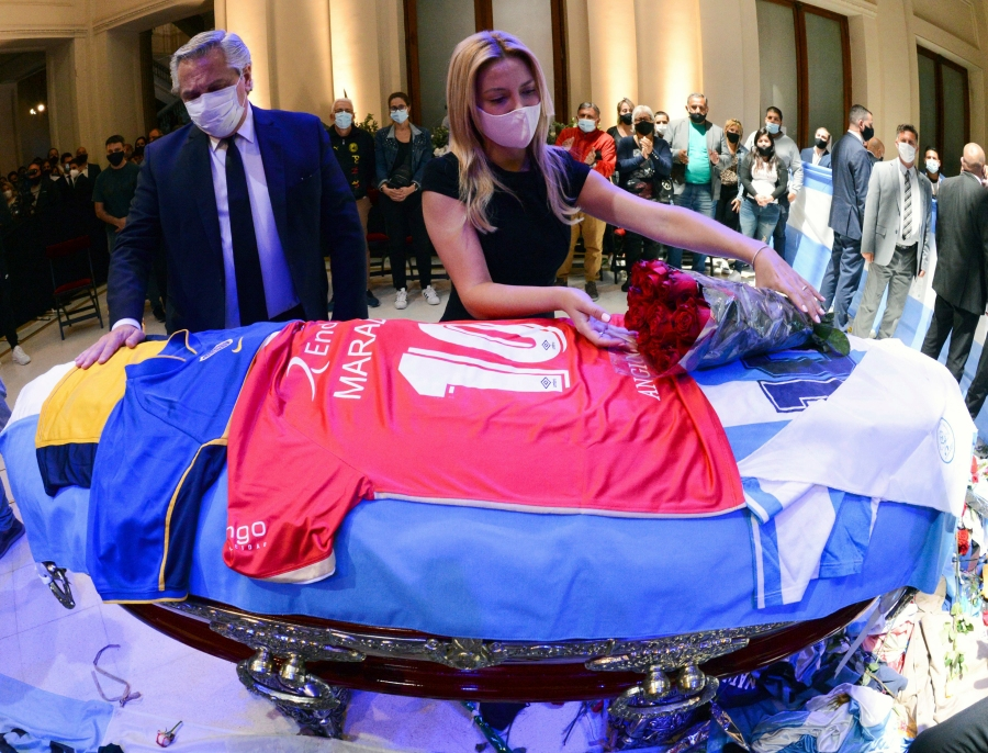 In this handout photo released by Argentina's Presidency, President Alberto Fernandez touches the coffin that contain the remains of Diego Maradona, while first lady Fabiola Yañez places a bouquet of roses on the casket adorned with his team jerseys, as they pay their final respects to Maradona, inside the presidential palace in Buenos Aires on Nov. 26, 2020. (Argentina's Presidency via Associated Press)